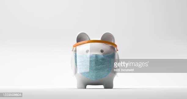 piggy bank wearing a surgical mask - sinal de emergência informação imagens e fotografias de stock