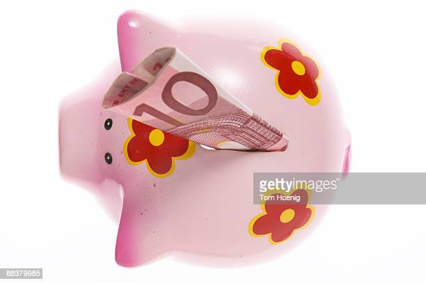 Piggy bank with ten Euro notes, close-up, elevated view