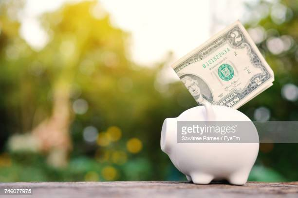 Piggy Bank With Paper Currency On Wooden Table Outdoors