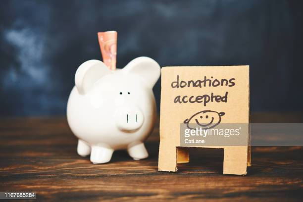 piggy bank with sandwich board reading donations accepted - charitable donation stock pictures, royalty-free photos & images