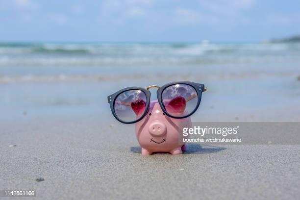 piggy bank with sunglasses on the beach - erschwinglich stock-fotos und bilder