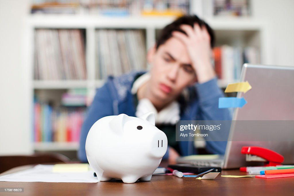 Piggy bank with young man worrying in background : Stock Photo