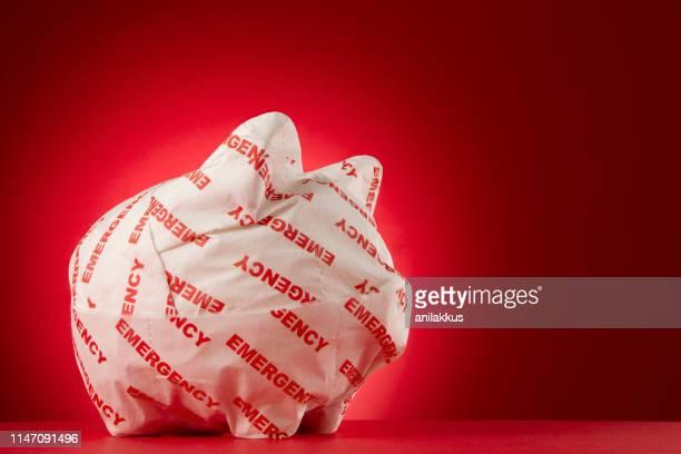 piggy bank wrapped with emergency paper - sinal de emergência informação imagens e fotografias de stock