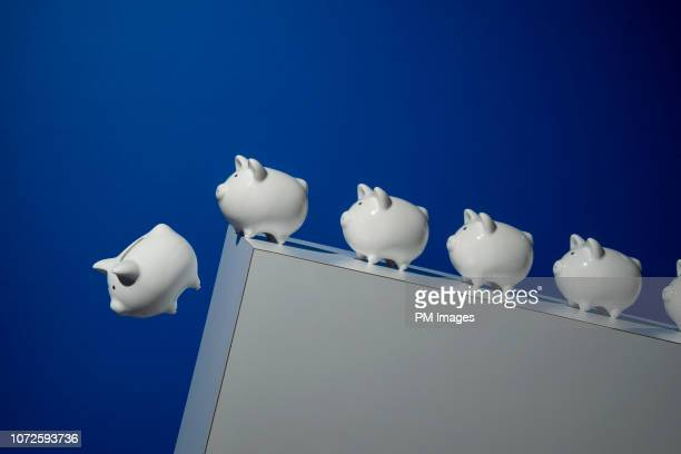 piggy banks going over a cliff - recession stock pictures, royalty-free photos & images