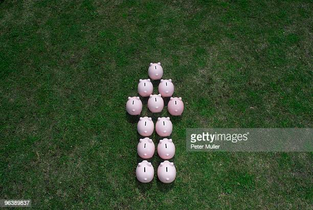 piggy banks in an arrow formation - prosperity stock photos and pictures