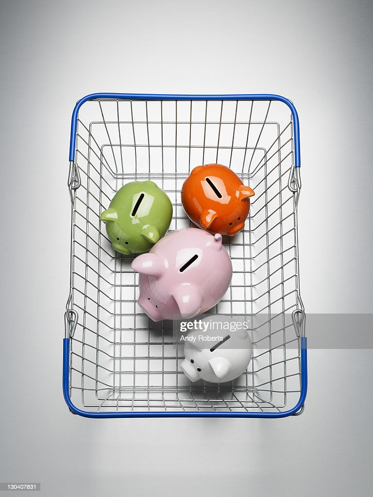 Piggy banks in shopping basket : Stock Photo