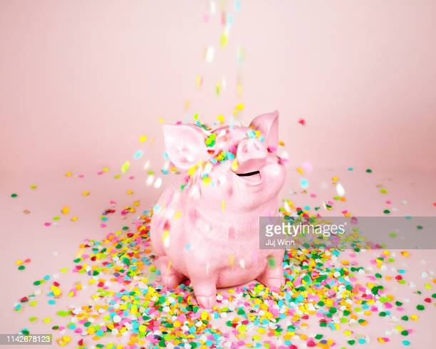 piggy coin bank with falling confetti - ersparnisse stock-fotos und bilder