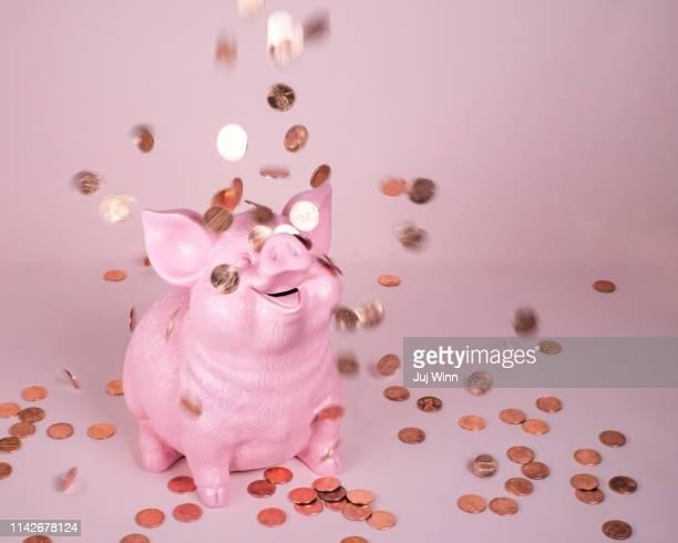 piggy coin bank with falling pennies - geld stockfoto's en -beelden