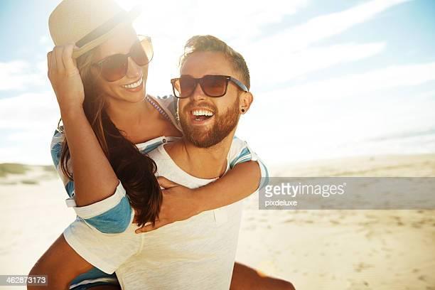 Piggyback couple at beach