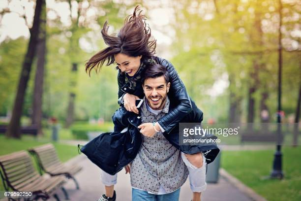 piggyback couple in the park - giochi erotici foto e immagini stock