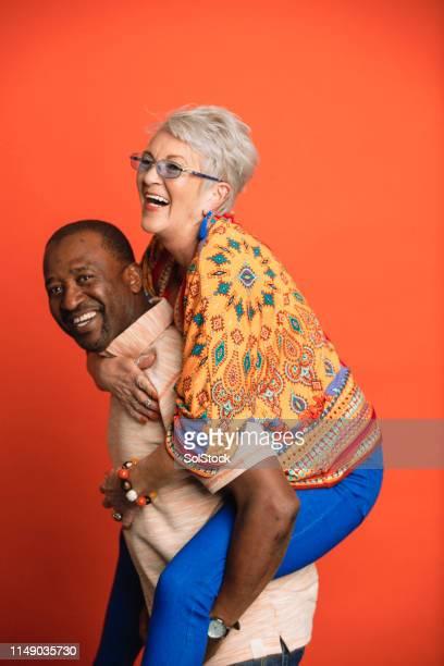 piggyback ride - studio shot stock pictures, royalty-free photos & images