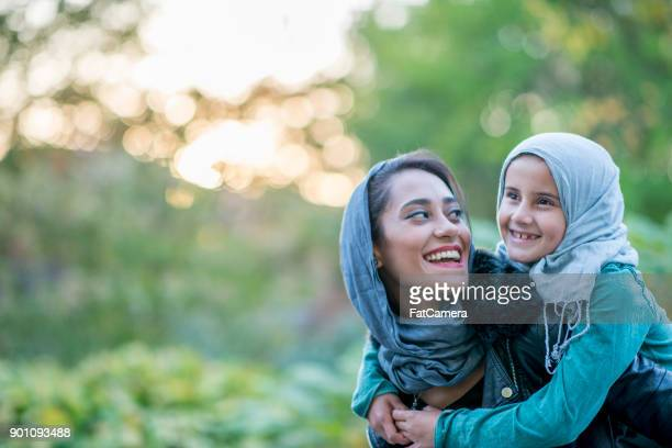 piggyback ride - muslim mother stock pictures, royalty-free photos & images