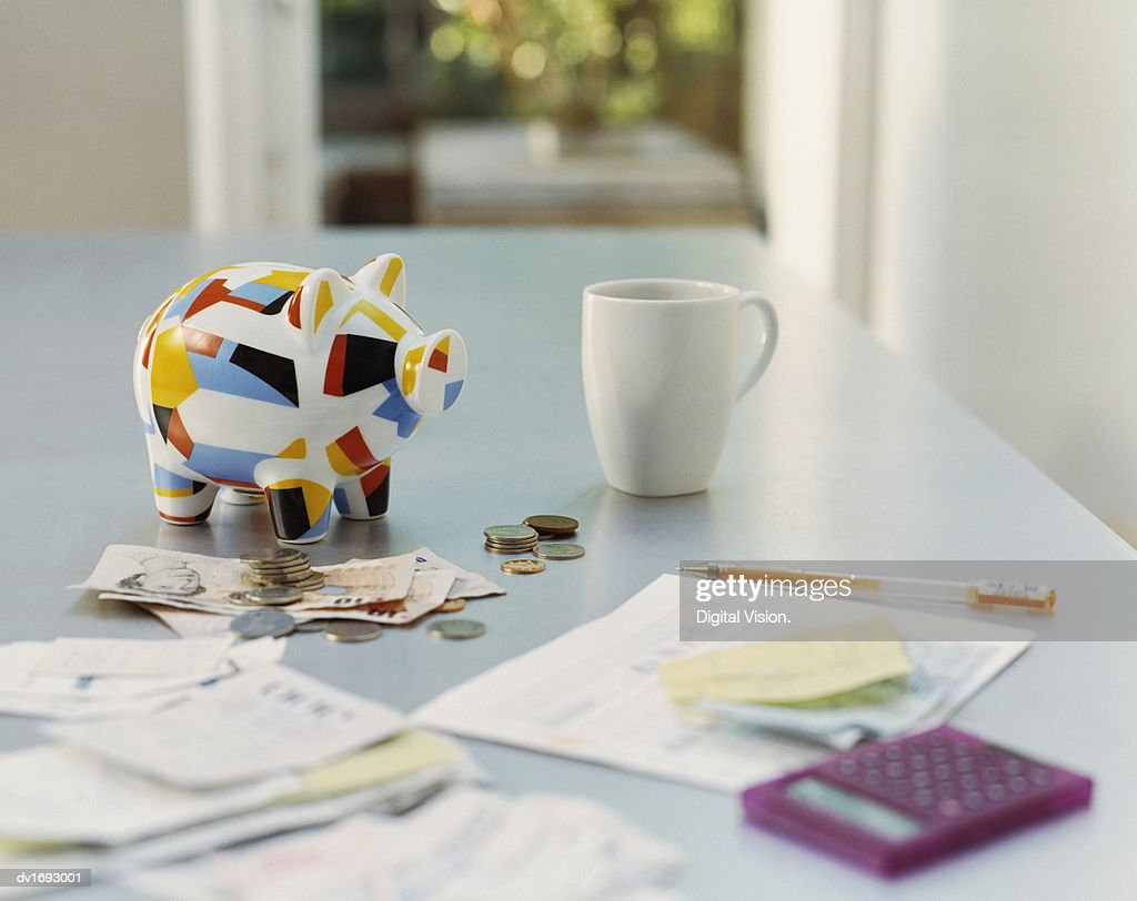 Piggybank, British Currency, Calculator, Receipts and a Mug on a Table : Stock Photo