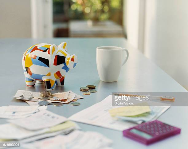 piggybank, british currency, calculator, receipts and a mug on a table - piggy bank stock photos and pictures