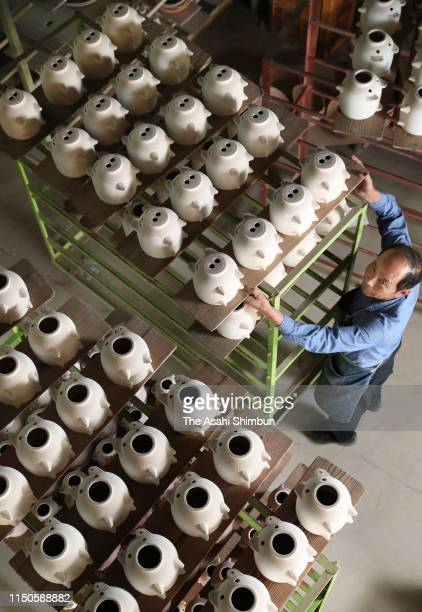 Pig-shaped mosquito coil holders await the finishing touches at the factory of pottery maker Matsuo Seitojo on May 20, 2019 in Komono, Mie, Japan....