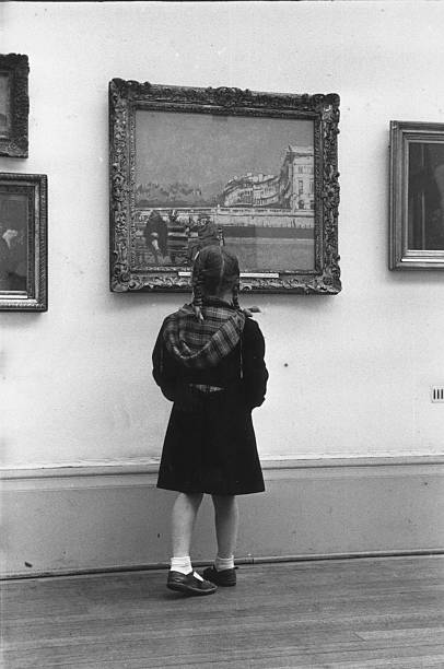 A pig-tailed schoolgirl studies a painting in the Tate...