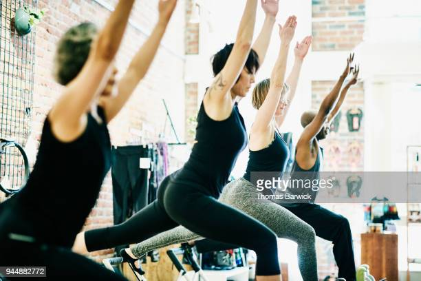 Pilates class doing russian splits with arms extended during fitness class in studio