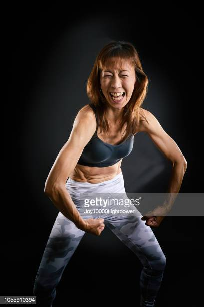 pilates coach woman shows her strong arm - chofu stock pictures, royalty-free photos & images