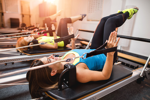 Pilates exercises on machines in a health club. - gettyimageskorea