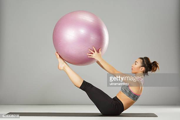 pilates stretching  training   woman practicing on a fitness ball - sports ball stock pictures, royalty-free photos & images