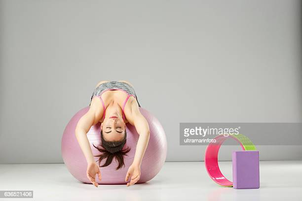 pilates stretching  training   woman practicing on a fitness ball - fitness ball stock pictures, royalty-free photos & images
