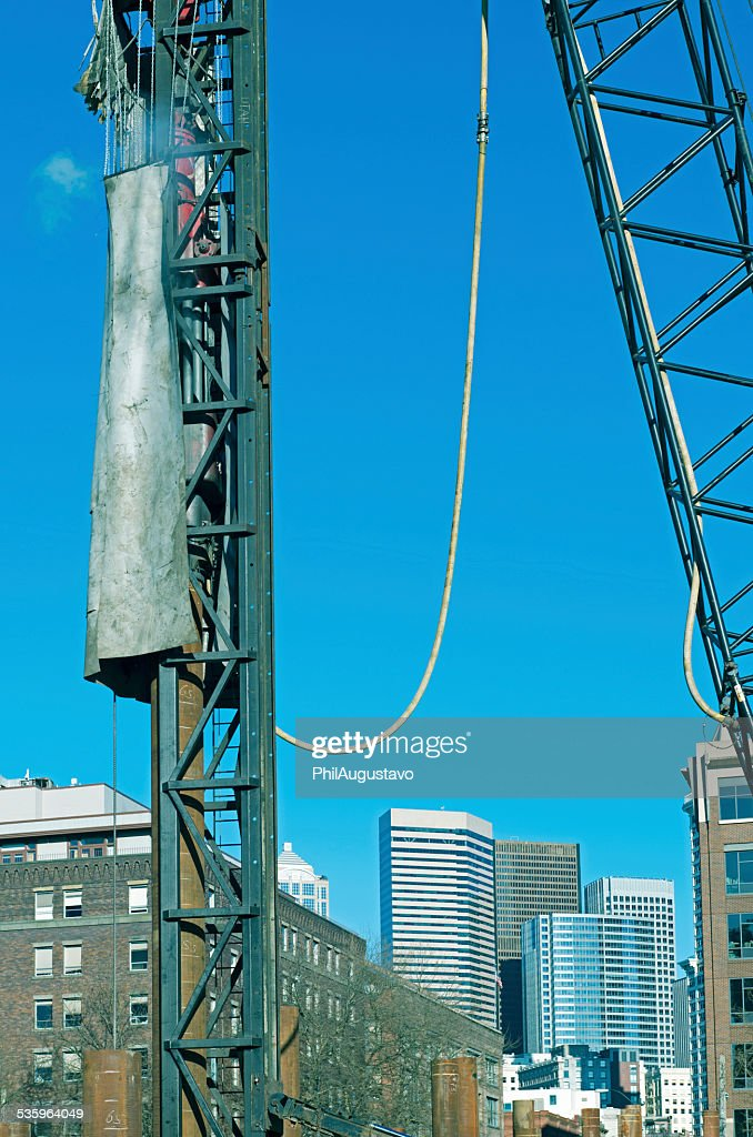 Pile driver driving poles for foundations of new building : Stock Photo
