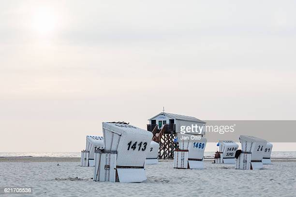 pile dwelling and beach chairs in st. peter-ording, germany - sankt peter ording stock-fotos und bilder