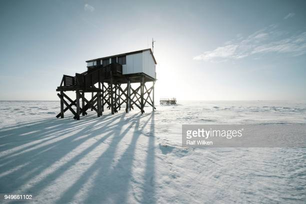 Pile dwelling in winter on a snow-covered beach, Sankt Peter-Ording, Schleswig-Holstein, Germany