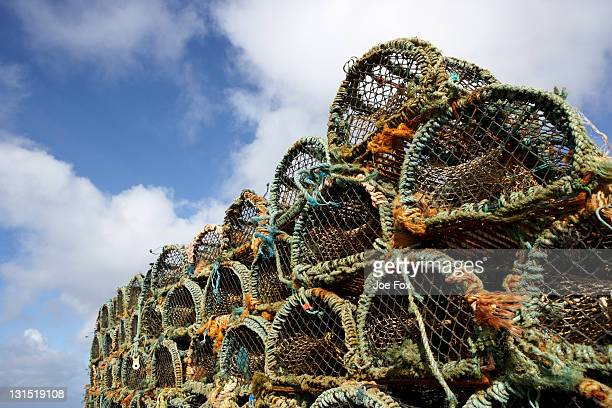 pile lobster crab fishing pots blue cloudy sky - crab pot stock photos and pictures