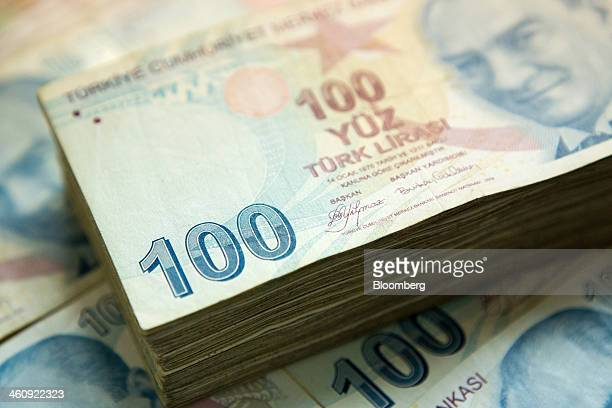 A pile of 100 denomination Turkish lira banknotes sit in this arranged photograph in Istanbul Turkey on Sunday Jan 5 2014 The Turkish lira is poised...