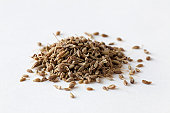 Pile of anise seeds on white surface