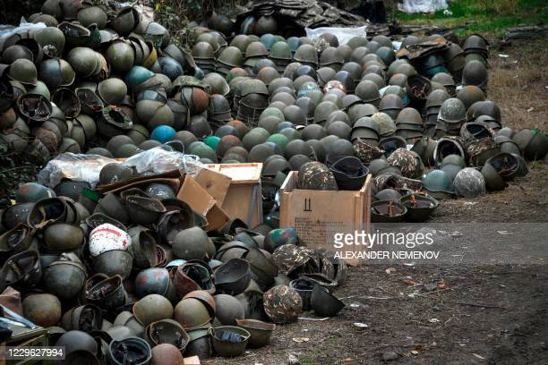 Pile of Armenian army helmets lie on the ground close to an Armenian Army barracks, where soldiers say there is no indoors storage space left, on...