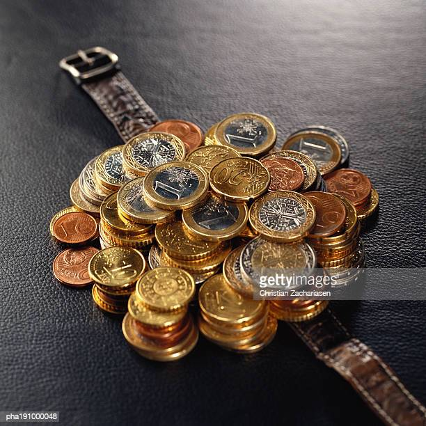 Pile of assorted coins on top of watch band.