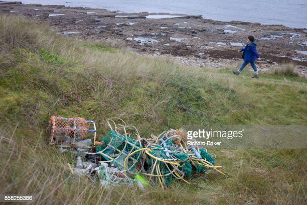 A pile of assorted ropes and fibrous cord and fishing pots await removal from the coastal landscape having been collected by volunteers from a beach...