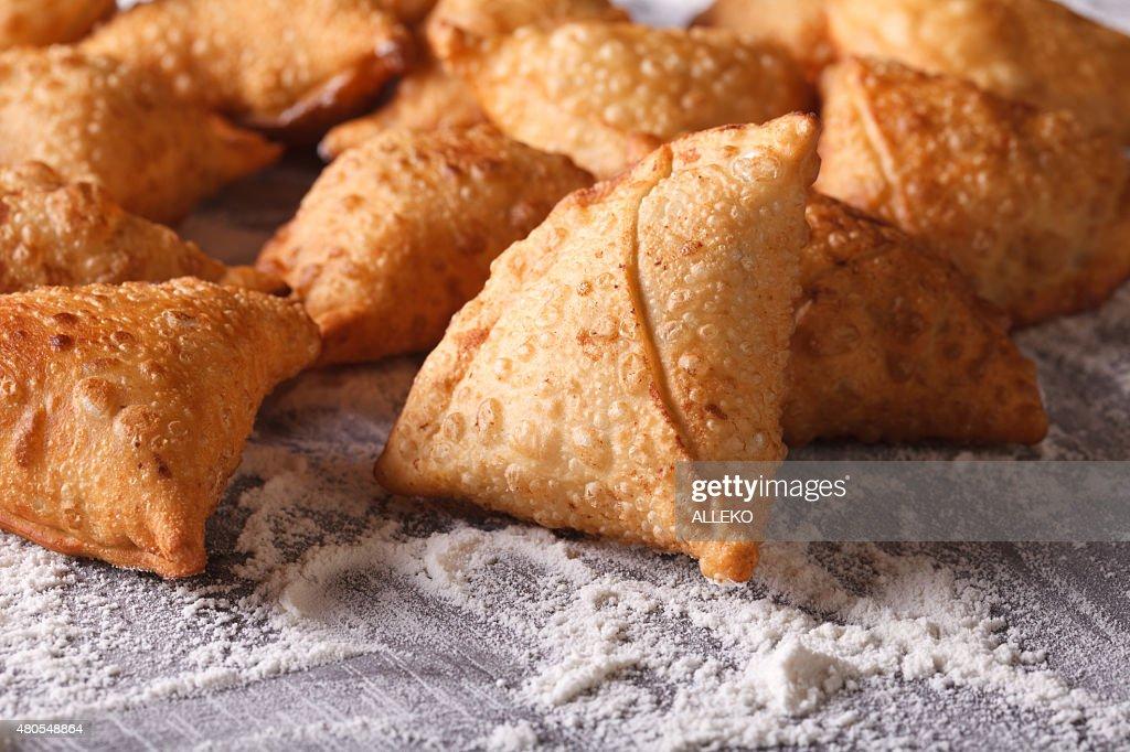 Pila de cocinar samosas floured en una mesa. TM : Foto de stock