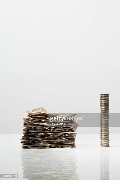 pile of banknotes and stack of coins - money laundering stock photos and pictures