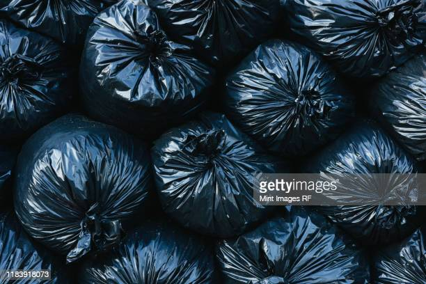 pile of black plastic garbage bags. - garbage dump stock pictures, royalty-free photos & images