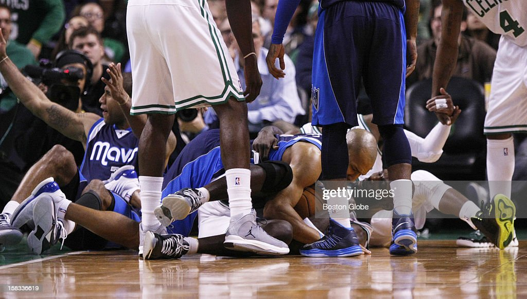 A pile of bodies, including Mavericks guard Derek Fisher (#6) and Celtics forward Kevin Garnett (#5) result after an offensive foul is called on guard Rajon Rondo (#9) in the fourth quarter as the Boston Celtics play the Dallas Mavericks during a regular season NBA game at TD Garden in Boston, Mass. on Wednesday, December 12, 2012.