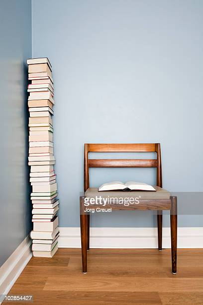 A pile of books, one book is lying on a chair