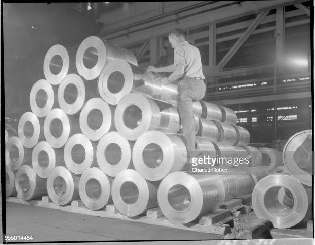 Pile of brass and copper strip A worker inspects large rolls of brass and copper strip in the ammunition division of the East Alton Works plant...