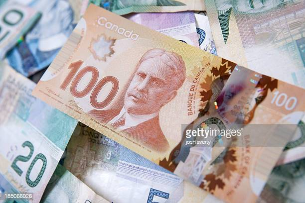 pile of canadian bills with one hundred dollars on top - canadian one hundred dollar bill stock pictures, royalty-free photos & images