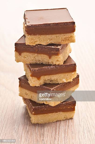 A pile of caramel shortbread on wooden table