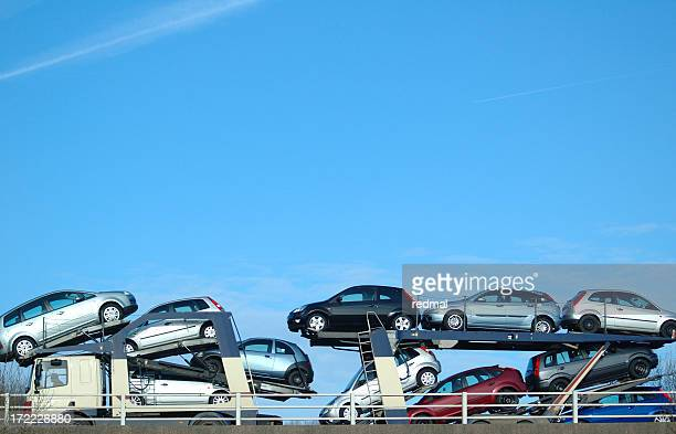 Pile of cars in a transporter over a clear blue sky
