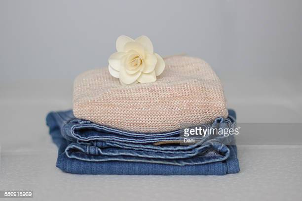 A pile of clothes with a flower on top