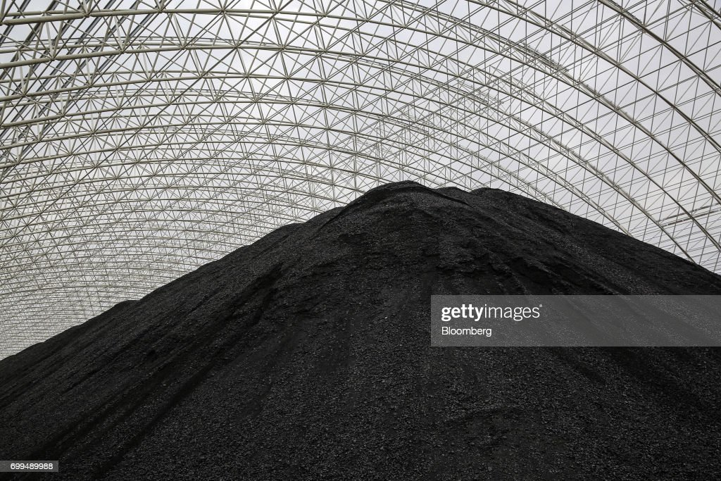 A pile of coal sits at the Sahiwal coal power plant owned by China`s stateowned Huaneng Shandong Rui Group at sunset in Sahiwal Punjab Pakistan on...