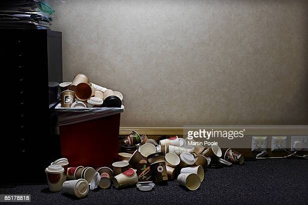 pile of coffe cups in corner of office