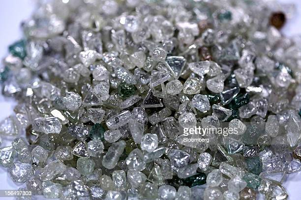 A pile of colorless and colored uncut diamonds sit on a sorting table during processing at DTC Botswana a unit of De Beers in Gaborone Botswana on...