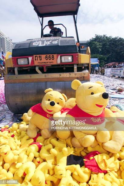 A pile of counterfeit WinniethePooh dolls await their fate in front of a steamroller crushing the counterfeit goods 26 November during Thailand's...