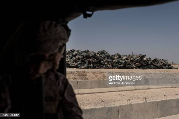 A pile of destroyed Afghan security vehicles sit outside the entrance to Camp Bost on September 11 2017 in Helmand Province Afghanistan About 300...