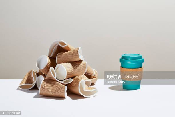 a pile of disposable coffee cups next to a reusable coffee cup - 使い捨て製品 ストックフォトと画像